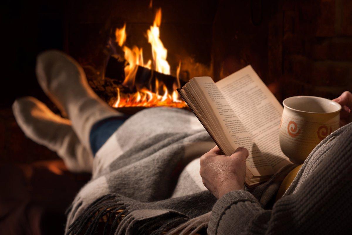 پتو پیچان در حال کتاب خواندن و چای خوردن درکنار شومینه