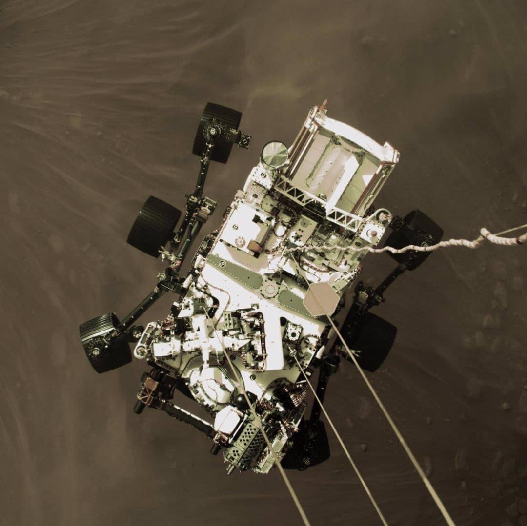 تصویر اول، تصویری با وضوح بالا از لحظه فرود مریخ نورد پرسیویرنس بر روی سطح سیاره سرخ با کمک سیستم اسکای کرین (skycrane) است.
