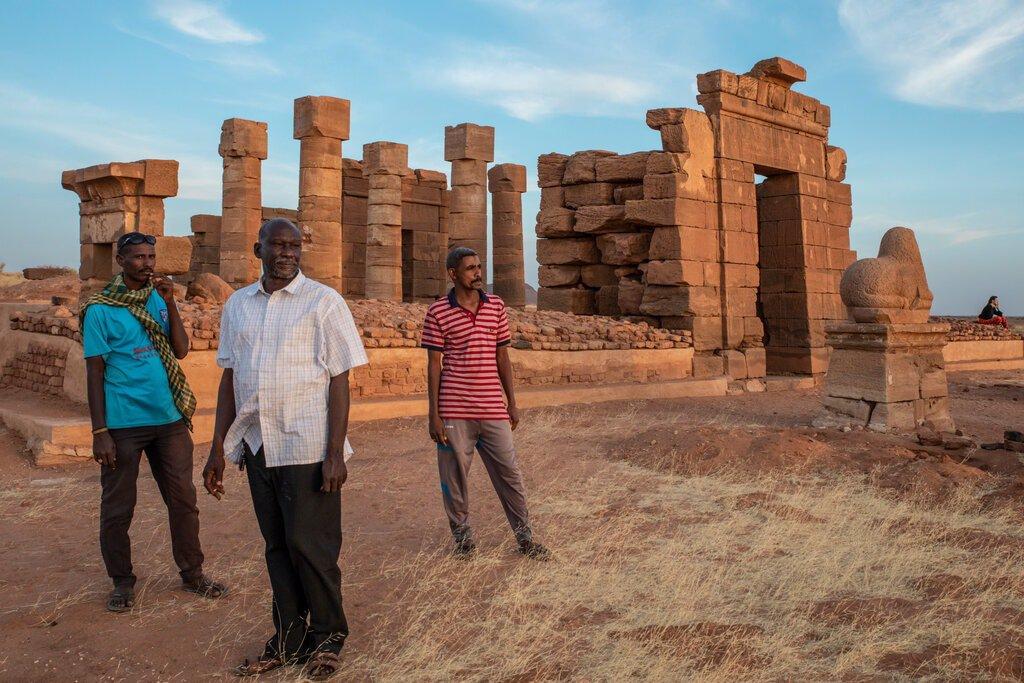 بازدیدکنندگان، همراه با یک راهنمای بومی، در خارج از معبد آمون.