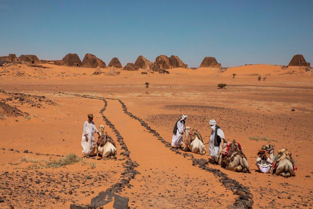 ساربانان شتر در نزدیکی اهرام در Meroe به دنبال مشتری می گردند.
